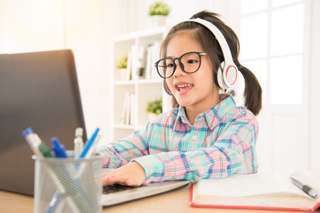 e-learning give preschool kids perfect study resource. asia cute sweet children typing with computer keyboard and listen headsets.