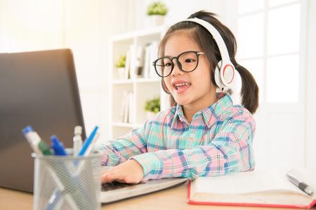 e ラーニングを与える幼児子供完璧な学習リソースです。アジアかわいい甘い子供のコンピューターで入力するキーボードし、ヘッドセットを聞きま