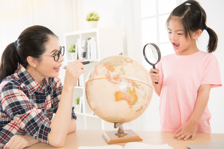enlarger: asian young kid girl observing and studying educational globe model with magnifying glass.  glasses woman pointing map preparing take daughter out.