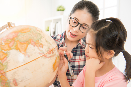 preschool teacher teaching cute girl kid about globe in geography class at school. young kid holding pen and focus on the map thinking. Imagens