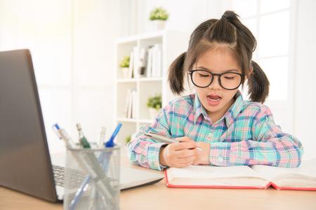 Asia escolar chino con gafas estudia inglés prueba de escucha con laptop y repite leer y escribir nota en libro. Estudia mucho en casa concepto. Foto de archivo - 81939719