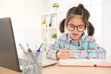asia chinese school girl with glasses study english listening test with laptop and repeat read and write note on book. study hard at home concept. Standard-Bild