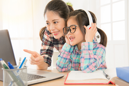 gentle kind woman carefully accompany cute preschool student studying and pointing content for girl in glasses and hands holding headsets.