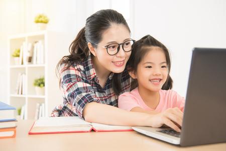 lach moeder laat haar kinderen weten hoe ze een laptop in de studeerkamer moet gebruiken. blij meisje opgewonden bij het typen van de eerste keer met haar favoriete moeder. Stockfoto