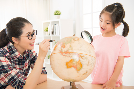 enlarger: joyful asian mom and chinese daughter preparing for the journey study the globe and choose a route of travel using pen pointing and magnifier searching. Stock Photo