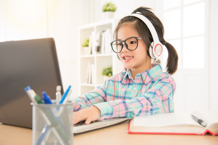 leisurely cute elementary kid seriously listening with headphones and typing on computer web. education learning technology concept.