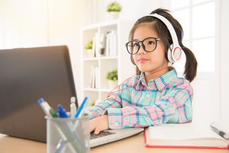 earpiece: asian chinese schoolgirl study with computer net website and wearing headsets listen foreign music. sweet kid thinking typing something. Stock Photo
