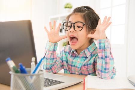asiatisches chinesisches Kind, das aufpassenden geöffneten Mund des Computers gefühlt und Hand nahe Gesicht zeigend. hübsches Kind studieren mit Internet.