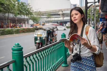 Tourist happy reading guide book. Woman traveler looking at copy space. Young female on vacation in bangkok, thailand. Asian girl near tuk tuk car on street.