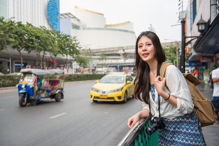Asian woman in bangkok city with a beautiful beaming smile down a busy street with taxi cabs and Thai traditional taxi tuk tuk car in downtown thailand.