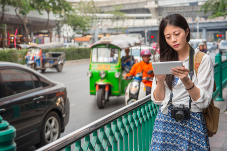 Woman on tablet smartphone walking on street in thailand. Bangkok busy traffic with thai traditional taxi tuk tuk car in downtown background. Asian woman using travel app or map during travel. Stock Photo
