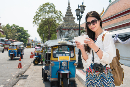 Tablet computer woman walking in bangkok, Asian woman using travel app or map during travel on street near Wat Pho in Thailand. Backpacker relaxing on a summer day.