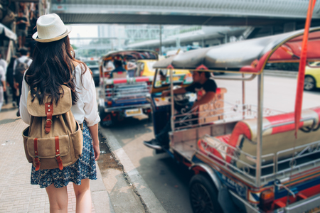 Woman tourist walking in busy bangkok street on thailand travel. Asian girl on street during Asia summer vacation. Thai traditional taxi tuk tuk car.