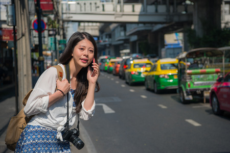 Chinese woman talking on the phone while walking on bangkok street, thailand. Smart backpacker using mobile app outside. Happy asian girl calling during eastern summer travel.