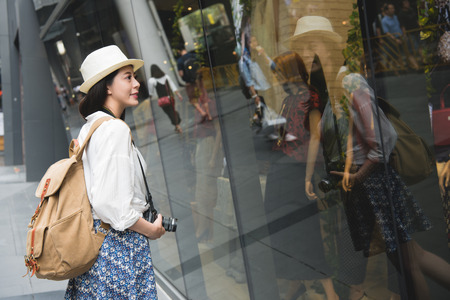Woman shopping in Hong Kong Central. Young lady looking at shop windows holding camera. Urban mixed race Asian Chinese woman shopper smiling happy living in city. Stock Photo