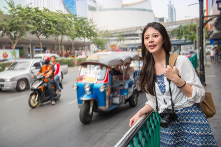 Woman tourist standing in busy bangkok street with a beautiful beaming smile on thailand travel. Asian girl on street during summer vacation. Thai traditional taxi tuk tuk car.
