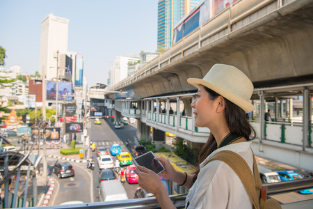 Traveler woman using tablet on flyover in bangkok, thailand. Young woman reading guide book map on tablet computer pc relaxing on busy traffic jam in background. Stock Photo
