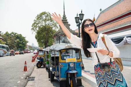 Hailing a tuk tuk taxi car on the street. Asian woman with hand up calling a taxi cab on bangkok street, thailand using phone app technology for passenger to request a ride online.