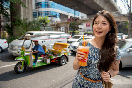 Lifestyle hipster asian woman drinking healthy traditional thai milk tea walking on downtown street of bangkok, thailand. Happy young asian girl with thai taxi tuk tuk car during summer vacation.