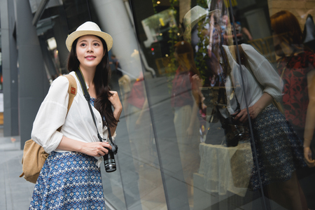 Shopping woman happy and looking away at outdoors. Shopper girl holding camera excited outside on walking street. Asian female model on bangkok, thailand