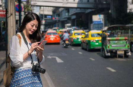 Asian backpacker woman using mobile phone app for car sharing service or using phone app to find directions and guide during travel on street in bangkok, thailand. Smartphone taxi concept. Stock Photo