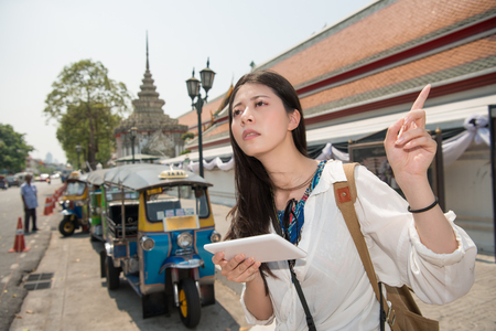 Travel woman with tablet app at street in bangkok, thailand. Asain girl traveling using touch tablet pc computer with guidebook or map in front of tuktuk taxi car near Wat Pho.