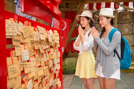 shinto: Happy Asian women, Japanese girls prayers on wooden plaques (ema) in japan. Pretty girlfriends backpacker praying hands and close eyes wish during travel vacation Stock Photo