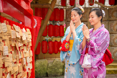 Asian girls wearing japan traditional kimono making a wish near Ema, Ema are small wooden plaques used for wishes by shinto believe. Girlfriends pray close eyes, red lantern background.