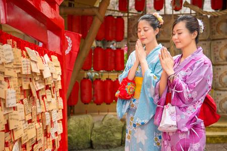 Ema, Ema 근처 소원을 만드는 일본 전통 기모노를 입고 아시아 여자는 shinto에 의해 소원에 사용되는 작은 나무 패를 믿습니다. 여자 친구는 눈, 빨간 랜