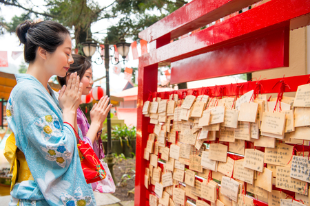 Tourist travel asian women friends dress japan kimono standing in front of Ema . Tourism concept with woman girlfriends write their wish on a wooden tablet and close eyes praying.