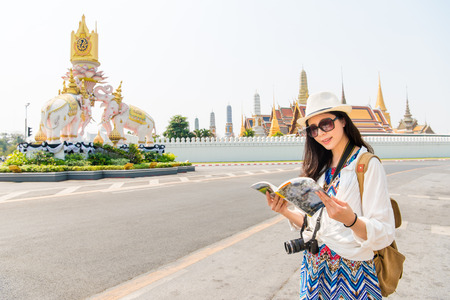 Bangkok, Thailand tourist with travel guide book on famous grand palace destination, Young woman traveler smiling happy vacation concept. 版權商用圖片 - 82514683