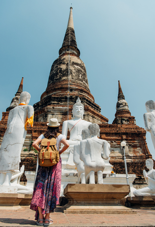 Young girl tourist from behind looking at statue view of Wat Yai Chai Mongkhon of Thailand at famous Ayutthaya tourism attraction during travel vacation in Bangkok. Asia summer holiday vacation.