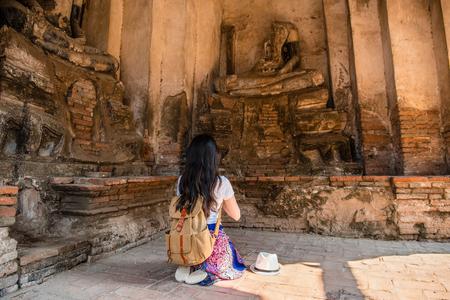 La muchacha turística que ruega delante de la estatua quebrada de Buda en Wat Chaiwatthanaram es templo viejo budista, parque histórico de Ayutthaya, Tailandia. Viajero mujer asiática disfrutando de sus vacaciones de verano. Foto de archivo - 82506114