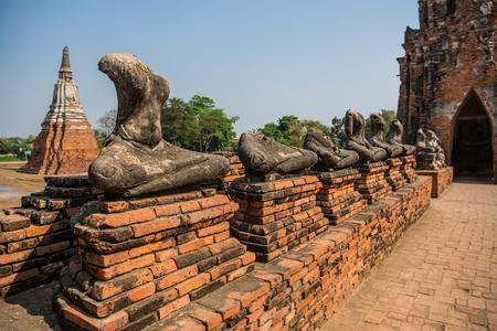 Old ancient buddha statue arrangement in Wat Chaiwatthanaram temple,Ayutthaya Historical Park, Thailand. vintage style. Sky background.
