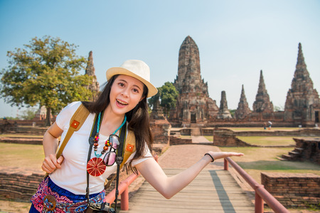 Backpacker asian woman smiling happy and do presenting gesture in front of famous tourist destination in Wat chaiwatthanaram temple of ayutthaya, thailand. Copy space.