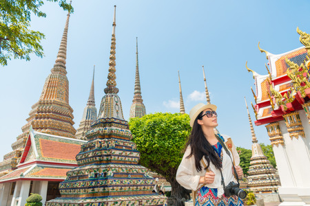 Bangkok city asian chinese woman enjoying view of wat pho temple shrine living a happy lifestyle walking during summer travel in Thailand. Female Asian tourist in her 20s.