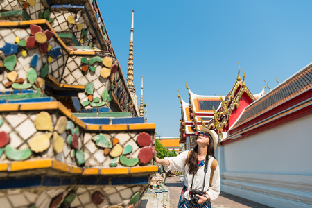 smiling pretty female student traveler touching famous buddhist building and looking viewing beautiful structure in Thailand travel on Bangkok wat pho temple.