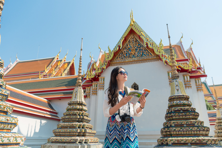 friendly beautiful female traveler holding guidebook reading travel information standing on wat pho temple and looking for route in Bangkok, Thailand. Imagens