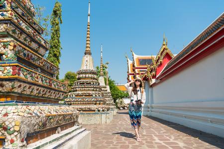 有名なワット ・ ポー寺院を訪問し、夏休みでバンコク、タイ旅行のマクロを表示する通路を歩いて幸せのエレガントな女性観光客の女の子。