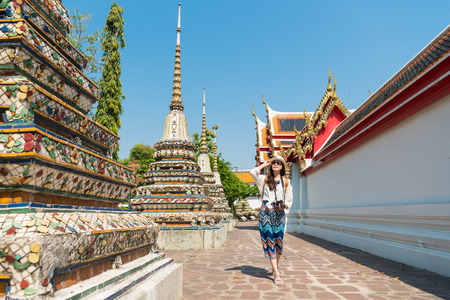 happy elegant female tourist girl visiting famous wat pho temple and walking on walkway viewing macro building in Bangkok, Thailand travel at summer vacation.