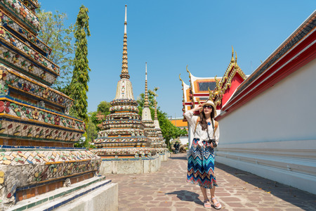 beautiful young woman traveler walking in wat pho temple on Thailand travel and holding professional camera visiting Bangkok at Asia summer travel.