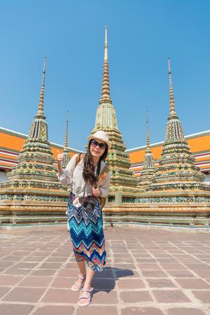 健康的なライフ スタイル旅行のコンセプト-幸せな女を与える楽しいを持っている親指を立てます。ワット ポー寺院、タイ ・ バンコクで手ジェスチ