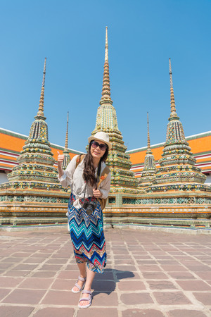 Healthy lifestyle travel concept- happy woman have fun giving thumbs up. Beautiful young Asian model showing hand gesture in wat pho temple, Bangkok, Thailand.