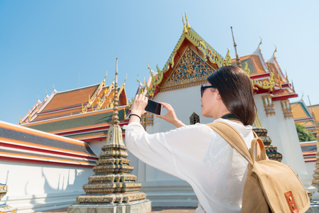 happy smiling woman using mobile smartphone taking picture on wat pho temple in Bangkok, Thailand travel at summer vacation.