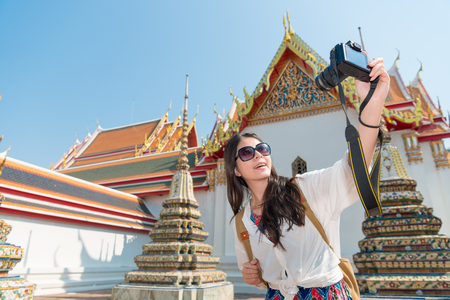 pretty leisurely girl holding camera and taking picture selfie with wat pho temple in Bangkok, Thailand travel at summer vacation holiday. Imagens