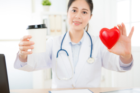 coffee cup and heart model showing caffeine causing people getting palpitations problem concept with selective focus photo of blur smiling female doctor in background.