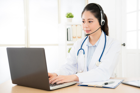 female doctor through internet conversation while looking at computer in hospital with patient and typing all content record in the computer data files medical insurance.