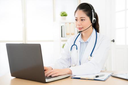 vrouwelijke arts via internet gesprek tijdens het kijken naar de computer in het ziekenhuis met de patiënt en het typen van alle inhoudsrecord in de computer gegevens bestanden medische verzekering.