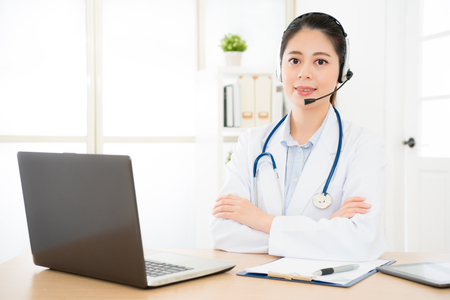 young female doctor agent practitioner working at the office and she answering phone calls online and scheduling examine medically time doctor of philosophy. Stock Photo