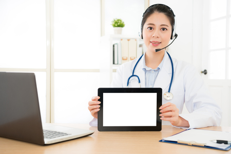 beautiful online doctor showing tablet computer with blank empty screen over copyspace smiling sitting on the hospital office giving service through internet tech.